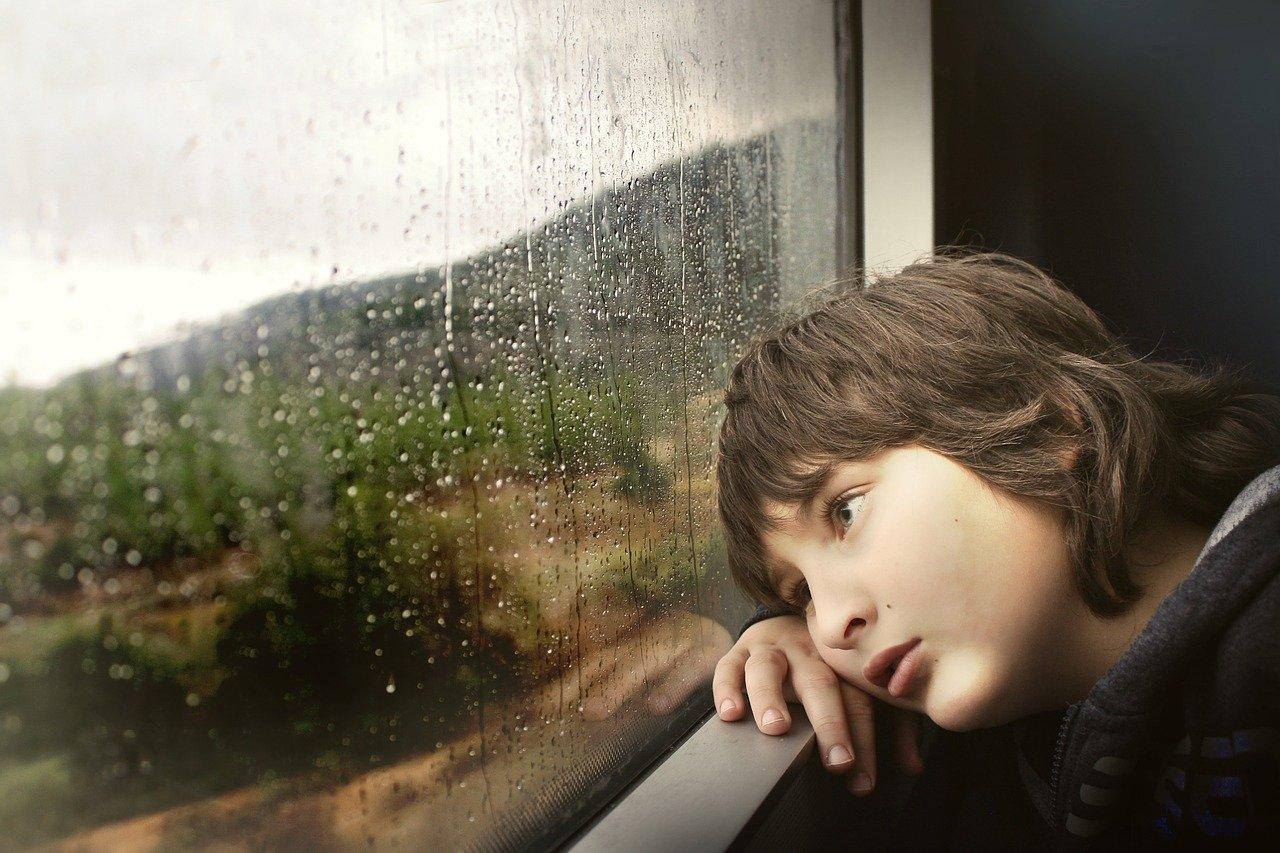 雨の日に外をながめる少年